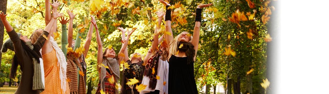 Kvinnor kastar färgglada höstlöv