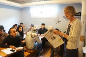 Lena undervisar asylsökande. Håller i en tidning