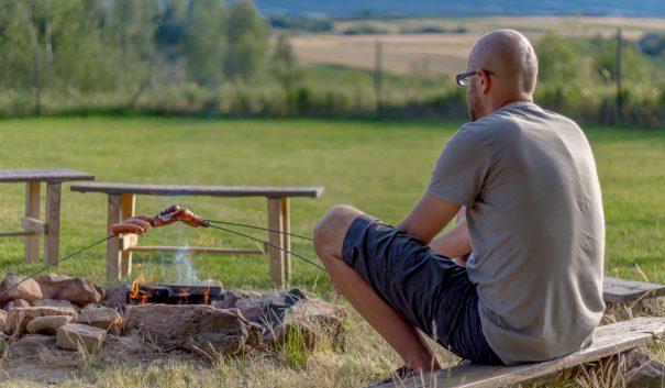 en man grillar korv över öppen eld