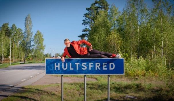 Person från humorgruppen Infallet ligger på Hultsfreds vägskylt