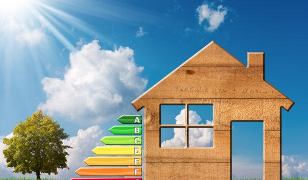Modell av trähus bredvid mått för energieffektivitet.