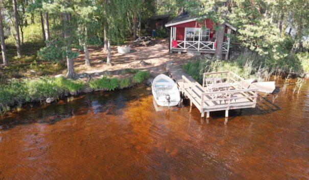 Röd stuga med brygga och båt framför